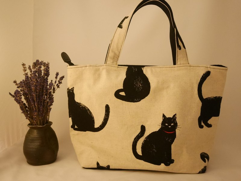 Elegant black cat out of a handbag