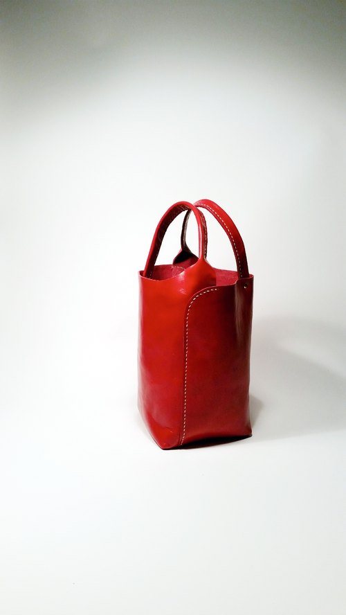 Bright red leather hand-stitched leather packet symmetry