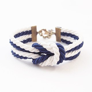 Double knot bracelet in navy blue and white with brass materials