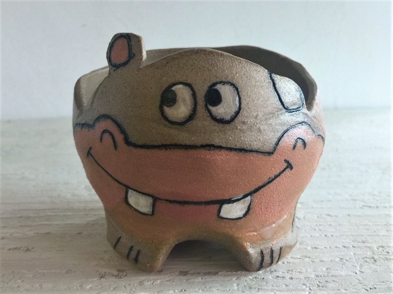 Smiling hippo has a foot and a pot of pottery_ pottery potted plants