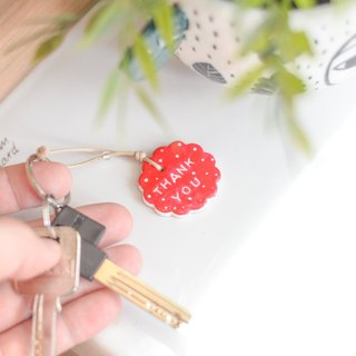 "The red key chain(key ring) with the word "" Thank you ""."