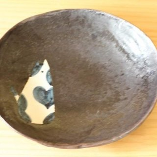 A black black-and-white brush's oval dish.