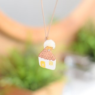 The little house handmade necklace with a white pom pom from Niyome Clay.