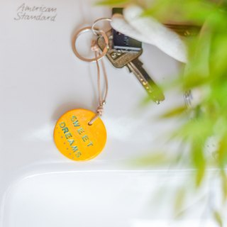 "The yellow key chain(key ring) with the word "" sweet dream ""."