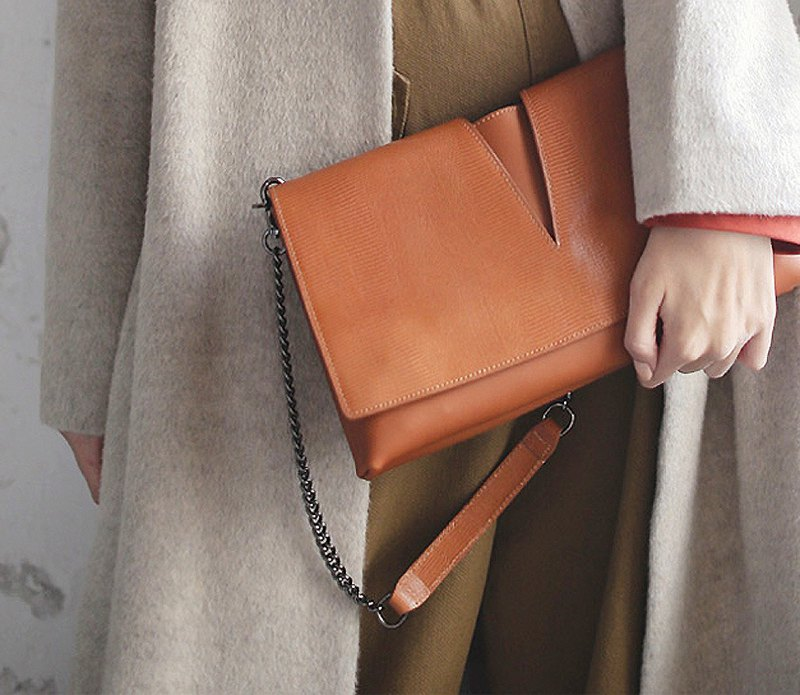Simple V fork hand holding the back leather bag orange brown