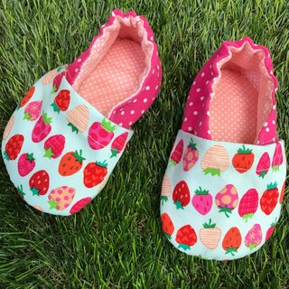 Rows of strawberries - toddler shoes. Baby shoes