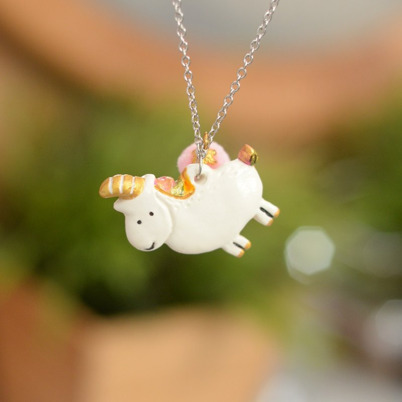 A little white sweet unicorn handmade necklace with a pink pom pom from Niyome Clay.