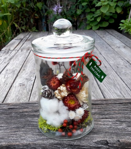 Glass jar of dried flower decorations Christmas Christmas music
