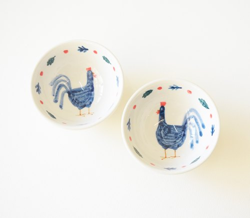Small hand-painted teacup - blue rooster and a small cup of red berries