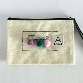 Purple green powder hair ball pin hand holding a small bag