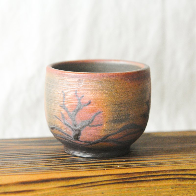 Wood fired pottery. Tea cup in the dead tree of winter