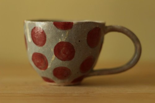 Cup of pulverizing hands and red dots.