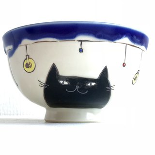 Rice cup with black cat and bare light bulb