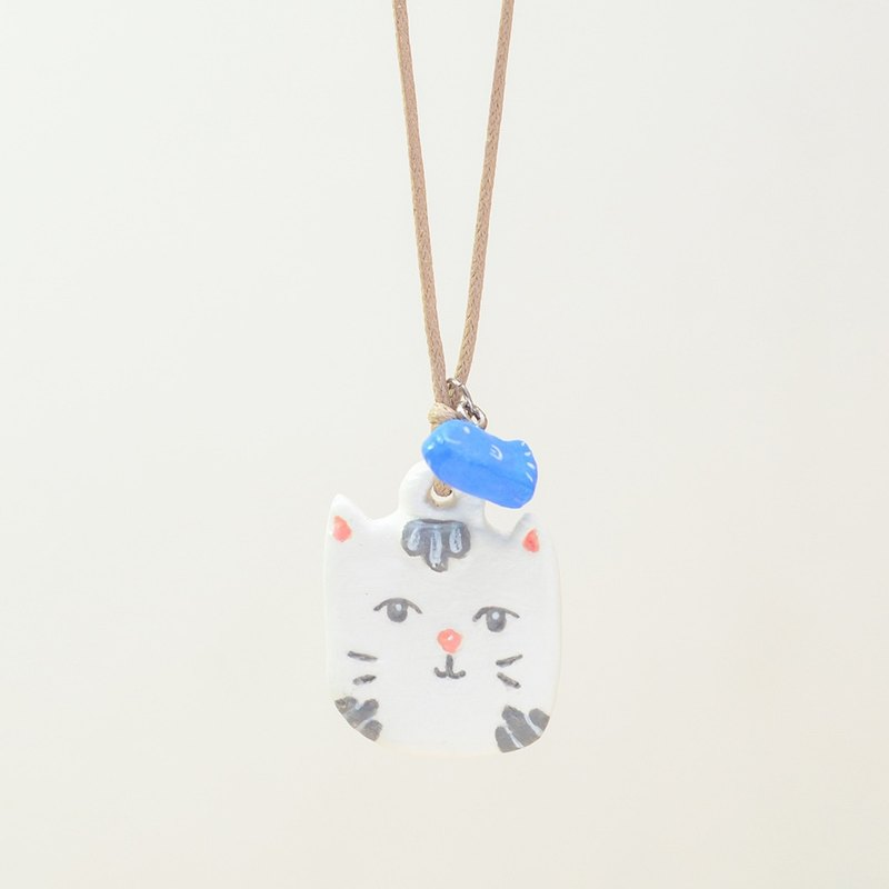 a little white cat with a tiny fish handmade necklace from Niyome clay.