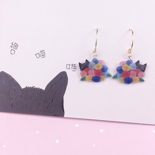 A pair of Black Cat Earrings hidden in flowers.