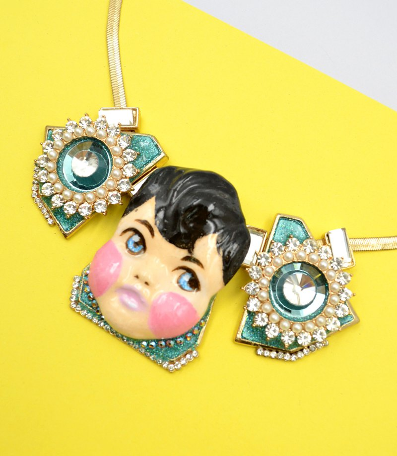 Hand-painted boy doll adorned with crystal gemstone necklace