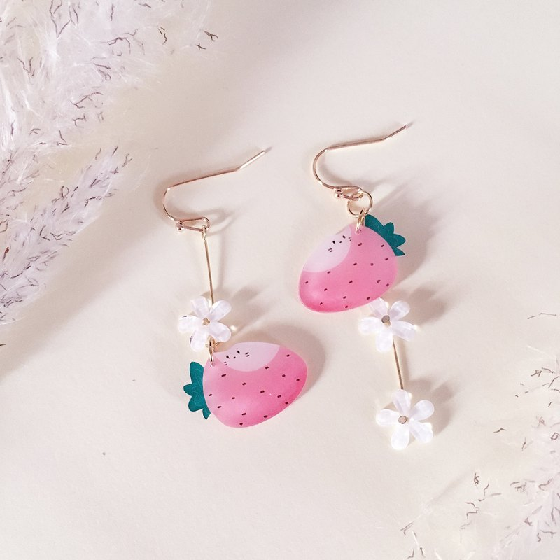 A pair of hand-painted strawberry earrings on the cake